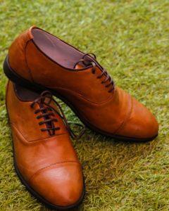 נעלי עור חומות אלגנטיות בתצוגה על דשא