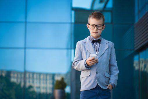 ילד קטן עם חליפה בצבע כחול בהיר ועניבת פרפר
